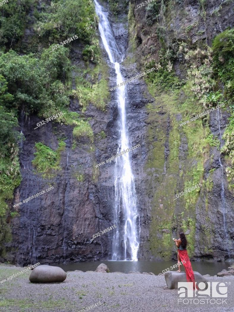 Stock Photo: Woman stands at Vaimahuta waterfall, one of three in Fa'aruma'i valley, Tahiti, French Polynesia.