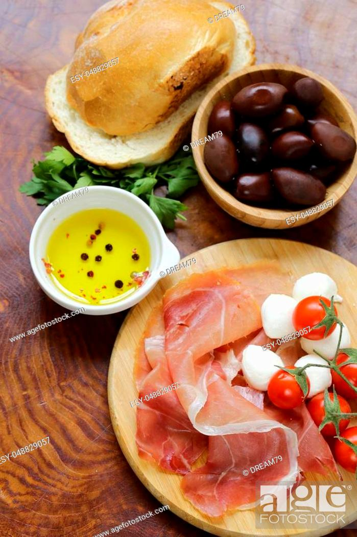 Stock Photo: Italian food - olives, parma ham, tomatoes, mozzarella cheese.