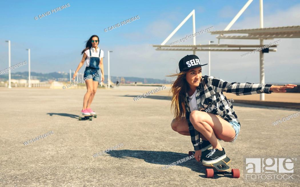 Stock Photo: Two young women longboarding on beach promenade.