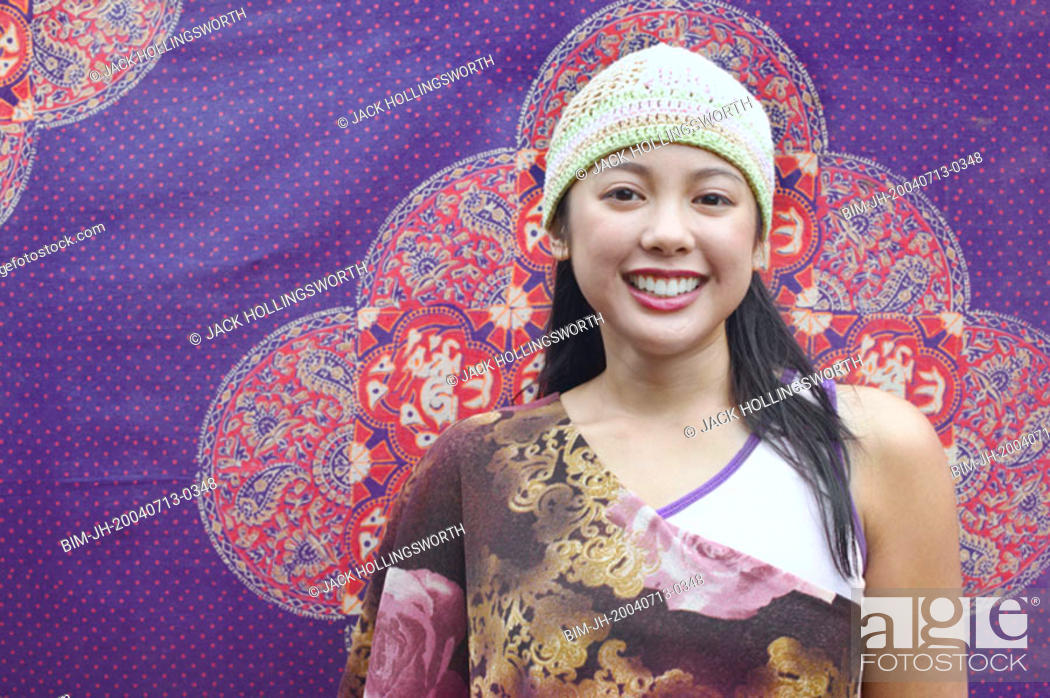 Stock Photo: Asian woman smiling in front of tapestry.