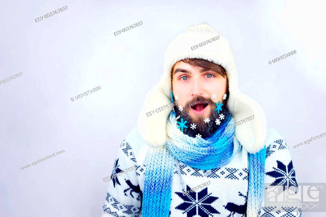 Stock Photo: Guy with trapper hat and blue scarf wearing beard decorated with small snowflakes, being surprised.