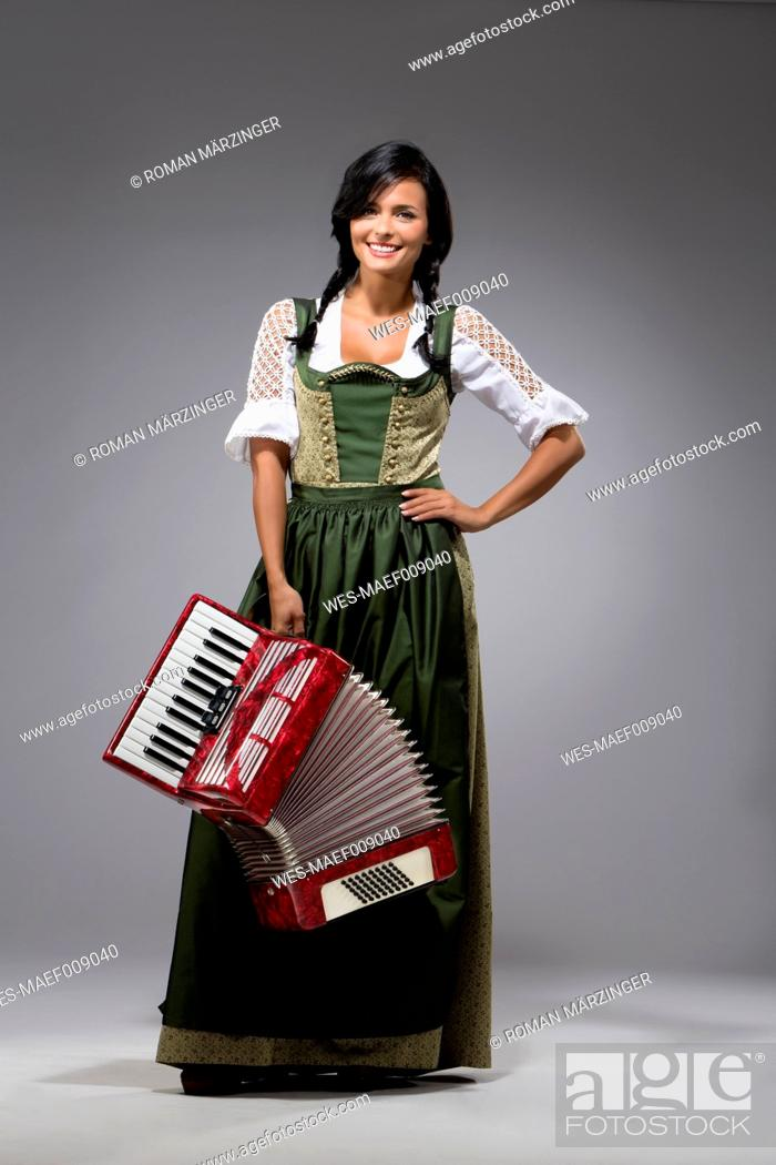 Stock Photo: Portrait of young woman with accordion wearing dirndl.