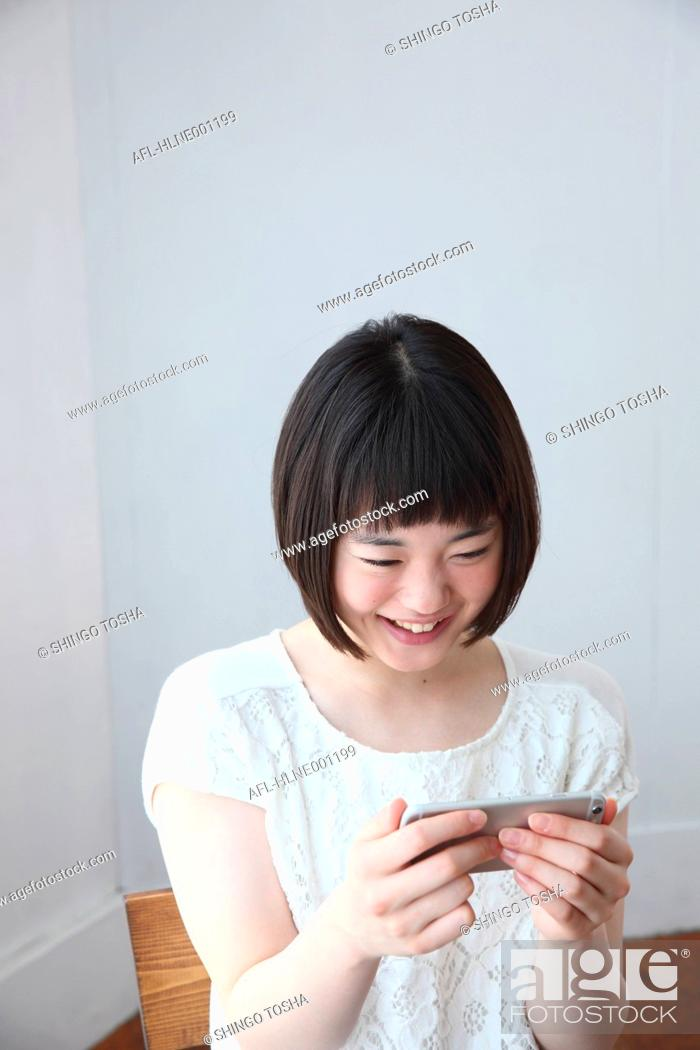 Stock Photo: Young Japanese woman with smartphone.