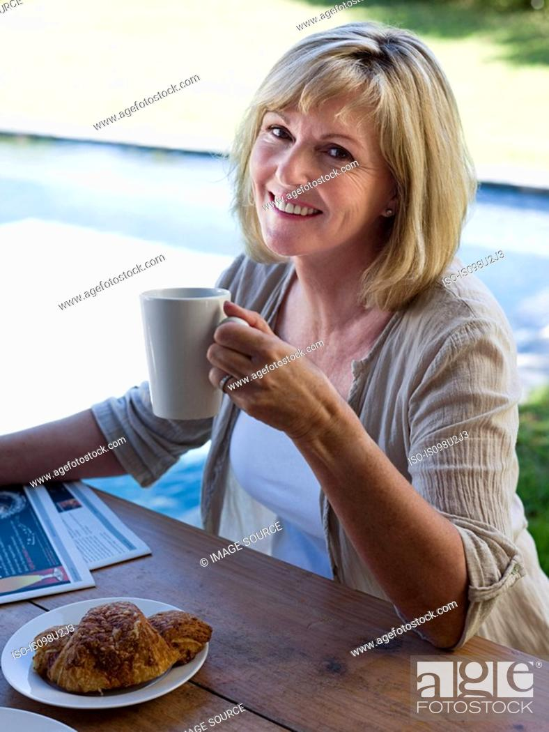 Stock Photo: Woman outdoors with coffee and breakfast.