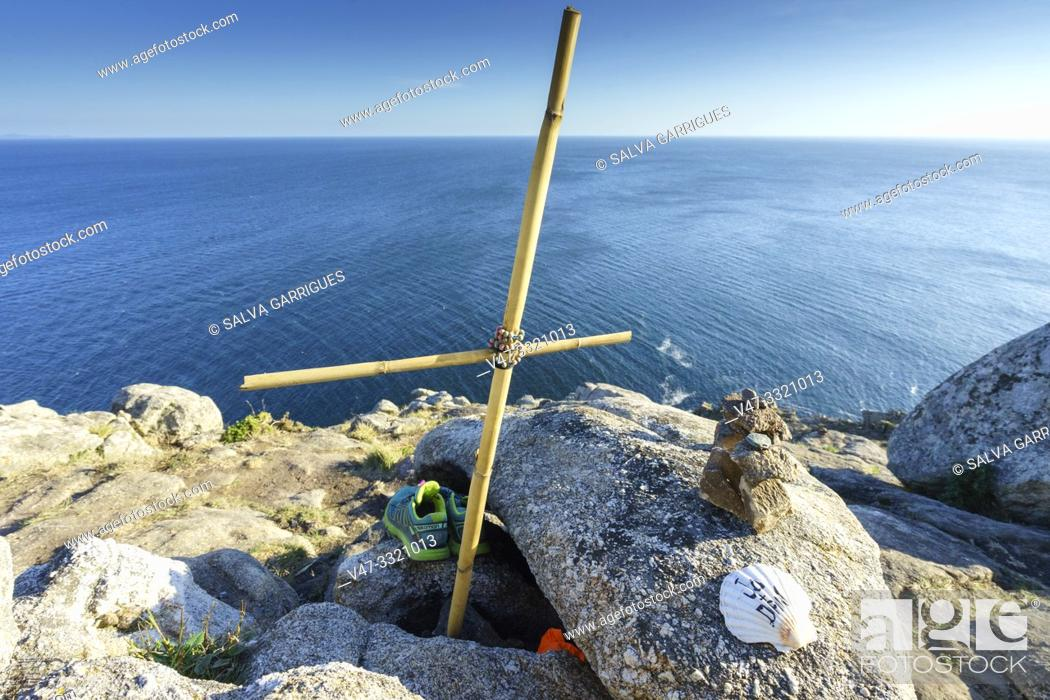 Stock Photo: Improvised crosses and scallops of pilgrims mark the end of the road at Cape Finisterre, A Coruña, Galicia, Spain.
