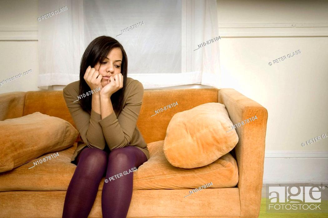 Stock Photo: Young woman sitting on her sofa.