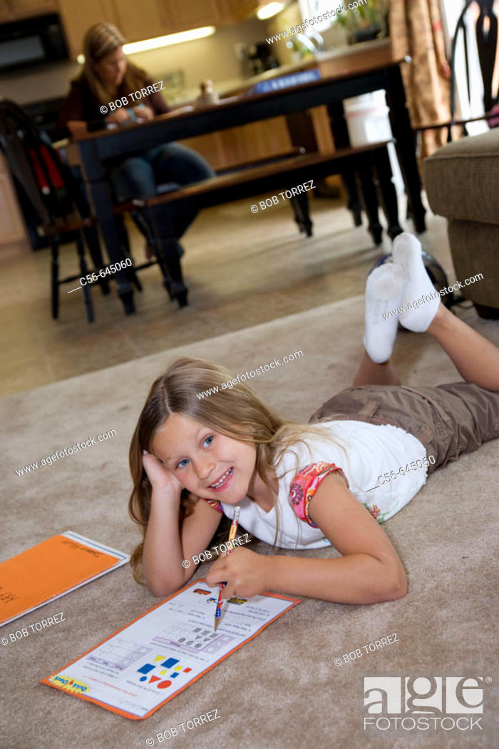 Photo de stock: smiling young girl does her homework on floor, mother in background.