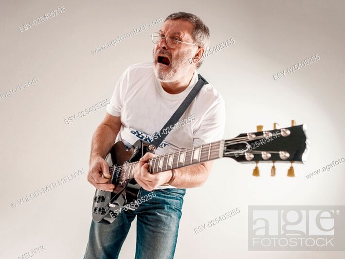 Stock Photo: Portrait of a guitar player exciting music on gray background.