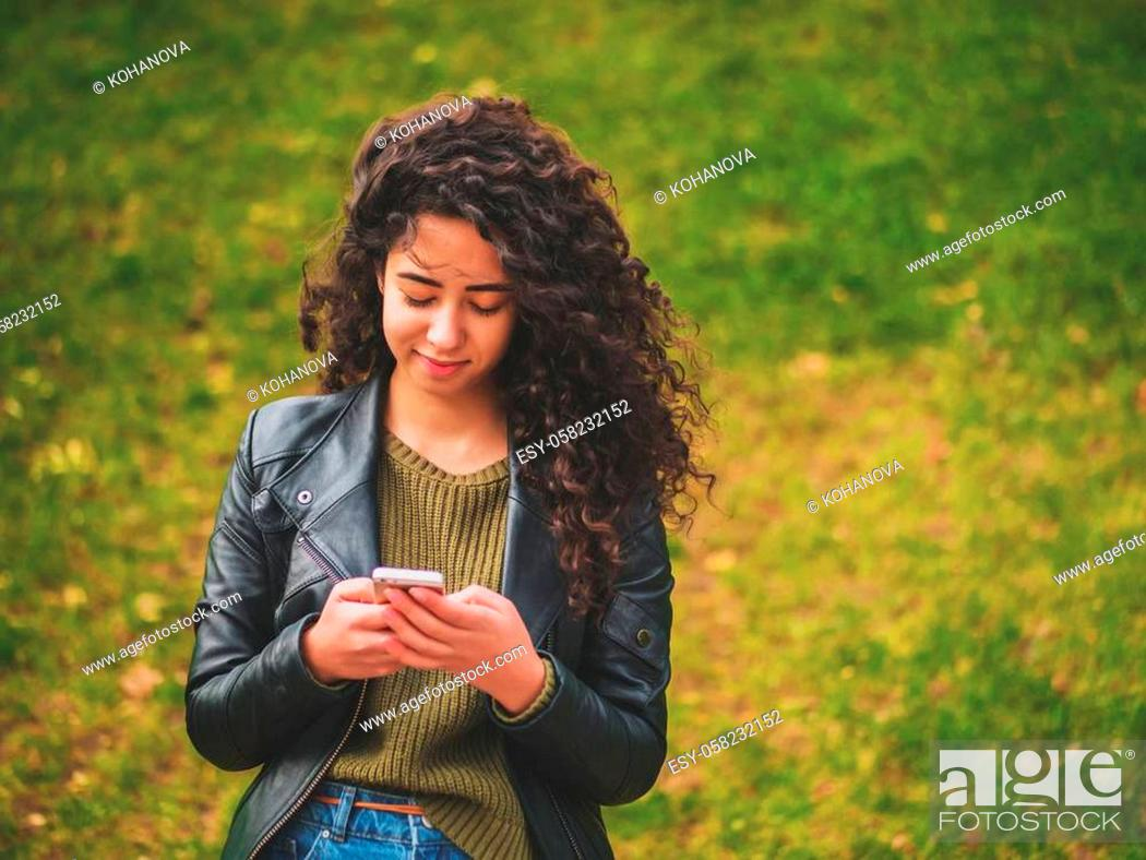 Stock Photo: Portrait of relaxed young lady in autumn park reading a text message on mobile phone. Beautiful young african girl with dark curly hair using cell phone.