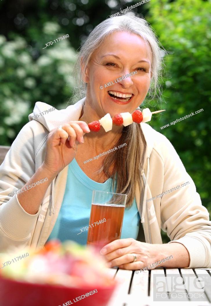 Stock Photo: elderly woman sitting in garden drinking ice tea.