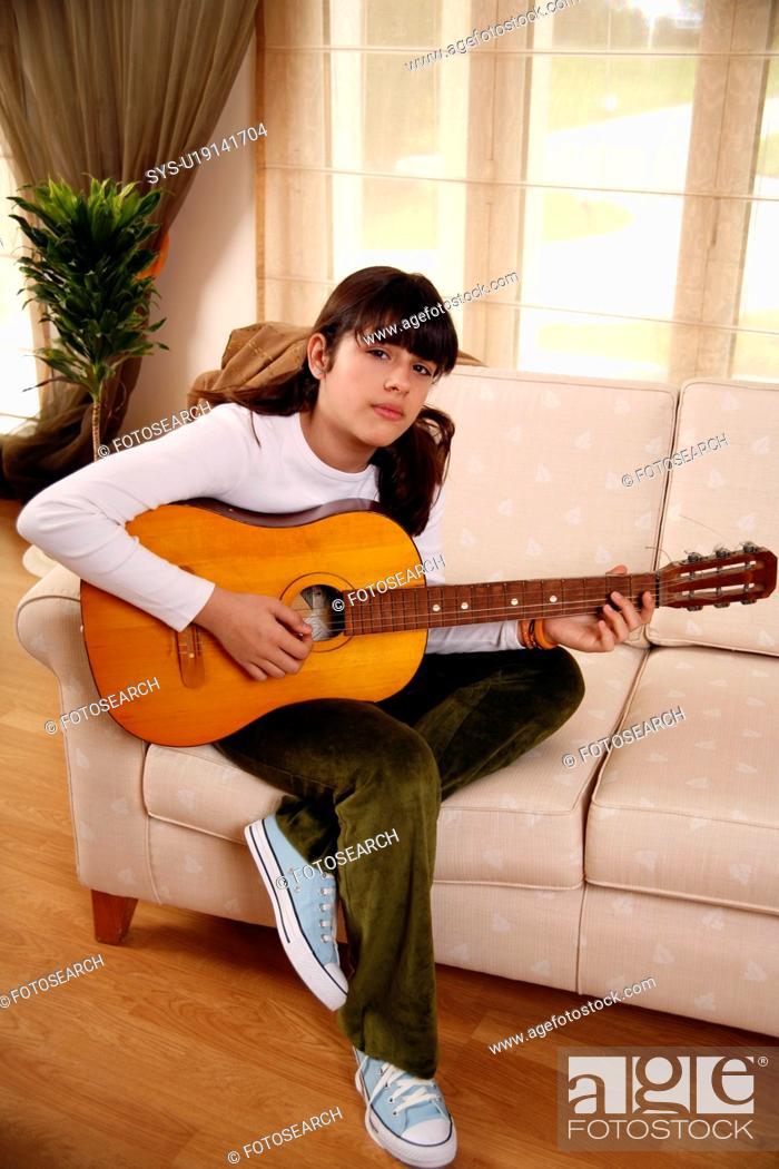 Stock Photo: Teenage girl playing the guitar.