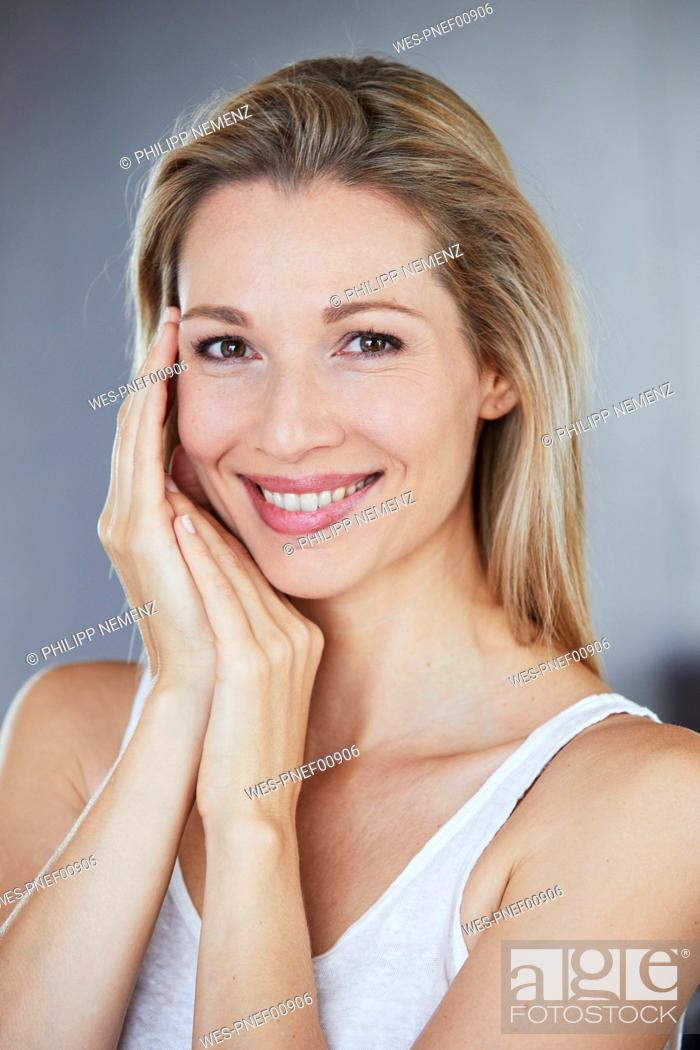 Stock Photo: Portrait of smiling blond woman in the morning.