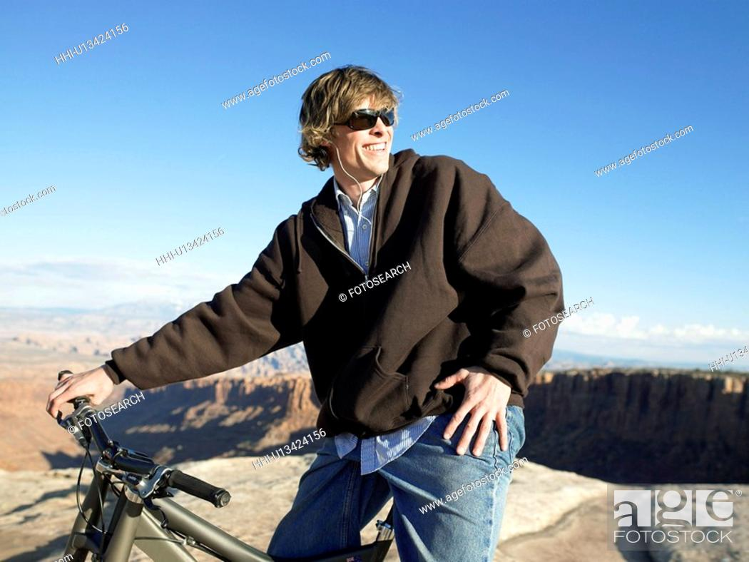 Stock Photo: Young man with mountain bike.