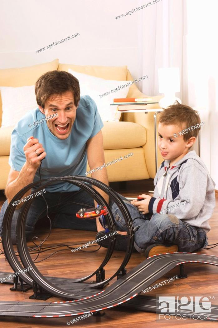 Stock Photo: Father and son 4-5 playing with toy racetrack.