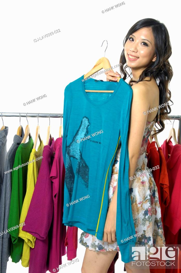 Stock Photo: Woman holding a top in a clothing store.