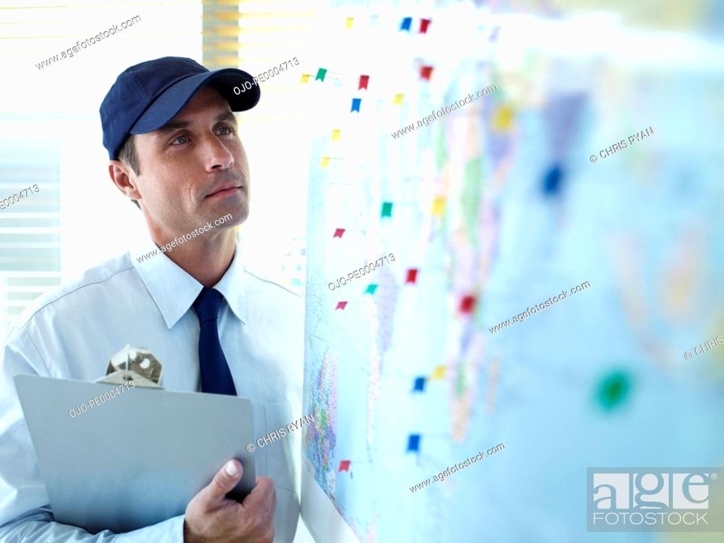 Stock Photo: Male delivery person with cap and clipboard looking at wall map.