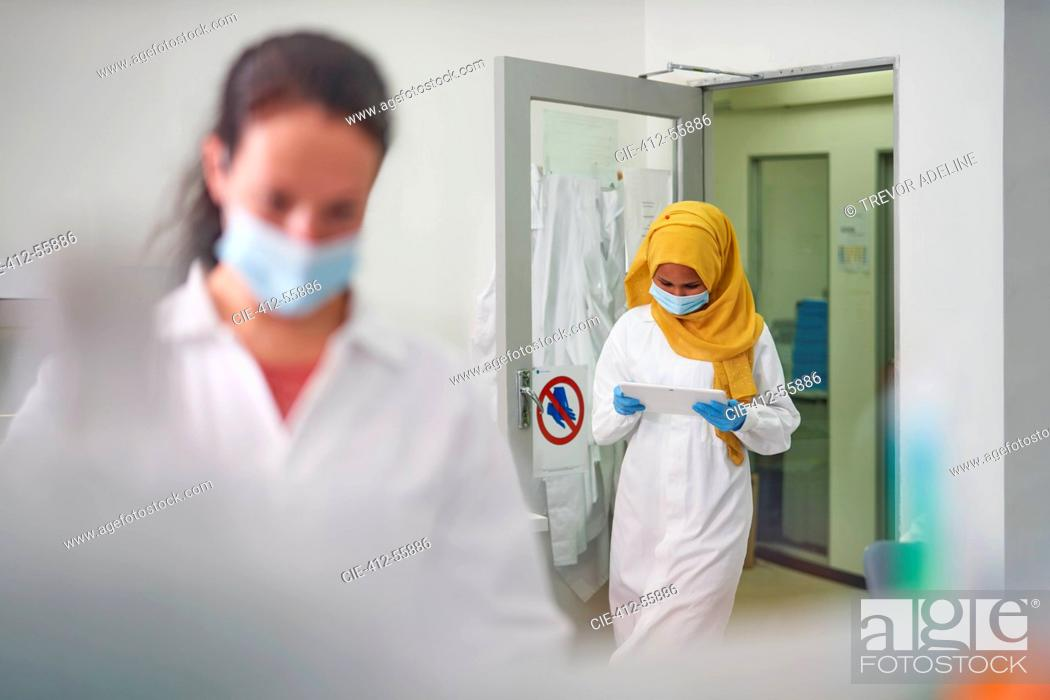 Stock Photo: Female scientist in face mask and hijab using digital tablet.
