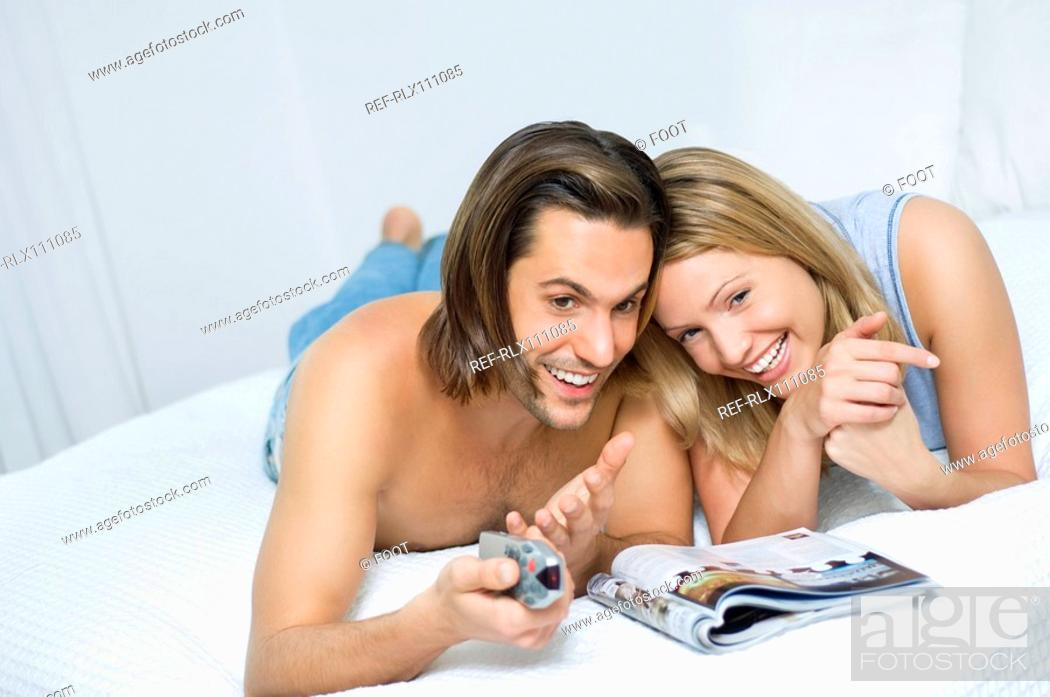 Stock Photo: Young couple in bed, watching television.