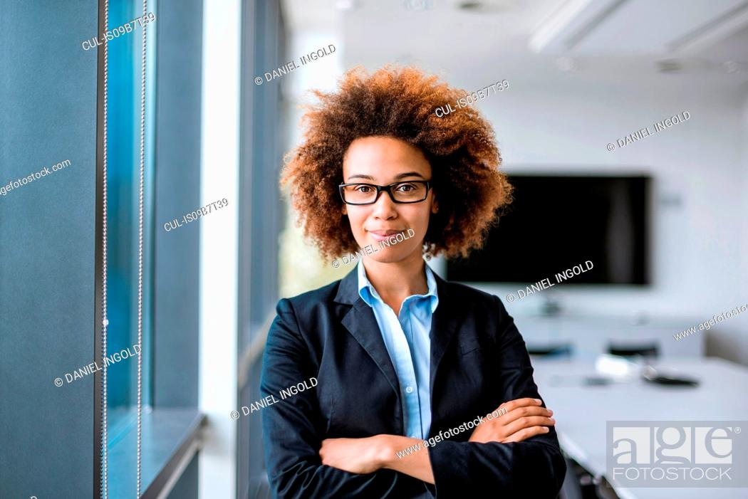 Stock Photo: Portrait of confident young businesswoman with arms folded in boardroom.
