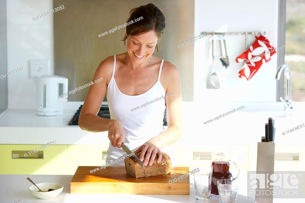Stock Photo: Woman in kitchen slicing bread.