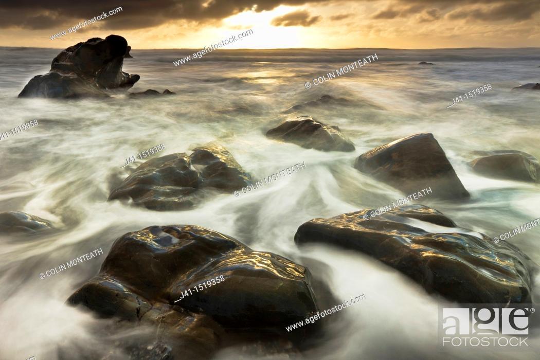Stock Photo: Sun sets beneath heavy cloud layer, seascape on rocks off Gillespie's Beach, Westland National Park, West Coast, South Island, New Zealand.