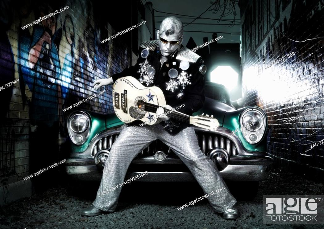 Stock Photo: Silver Elvis with a guitar and a retro car in a graffiti painted street  Performing artist Peter Jarvis from Toronto Canada.