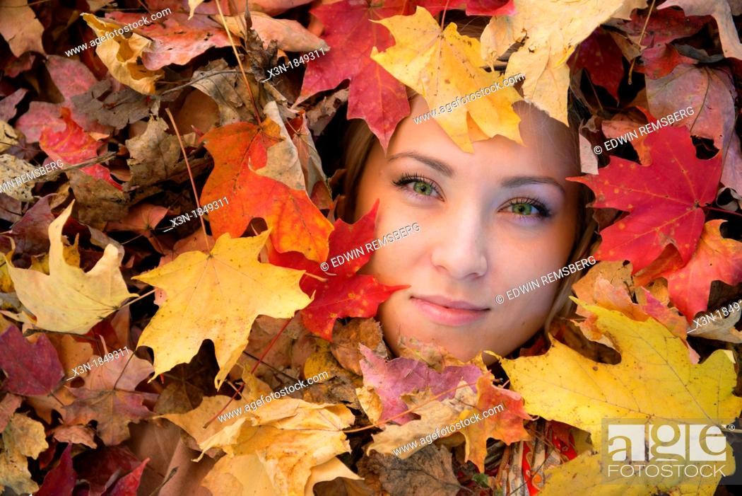 Stock Photo: Blonde haired woman outdoors in leaf pile.