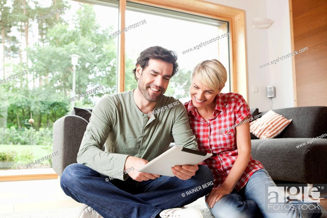 Stock Photo: Germany, Bavaria, Nuremberg, Mature couple using digital tablet in living room.