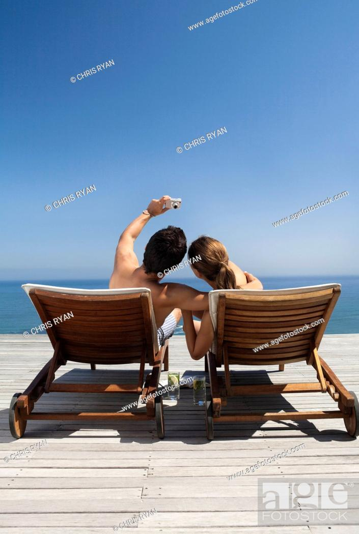 Stock Photo: Couple in lounge chairs taking self-portrait on patio.