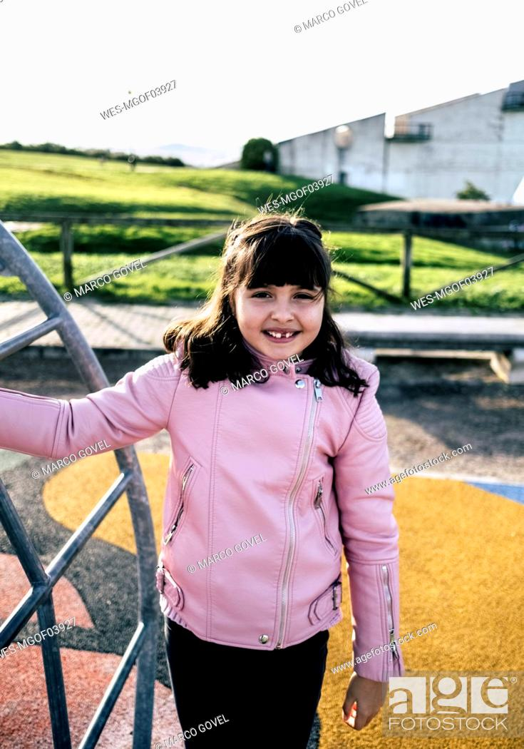 Stock Photo: Portrait of smiling girl wearing pink leather jacket on playground.