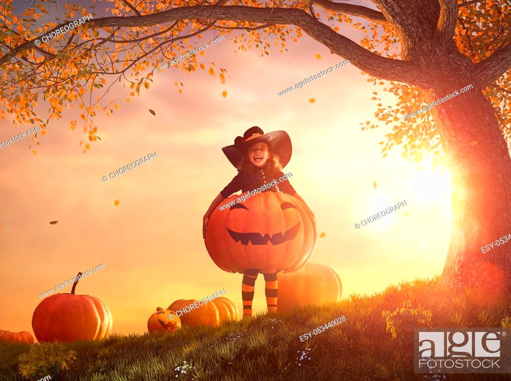 Stock Photo: Happy Halloween! Cute little witch with a big pumpkin. Beautiful young child girl in costume outdoors.