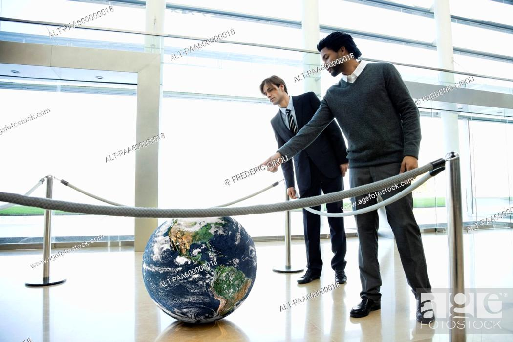 Stock Photo: Businessmen looking at ball in lobby.