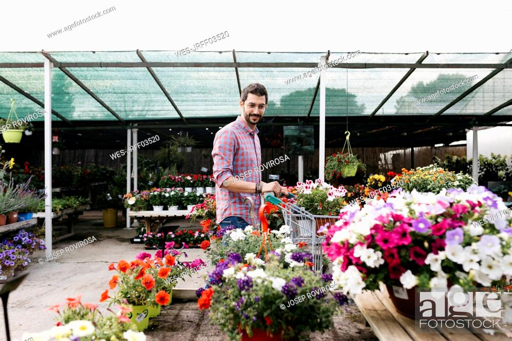 Stock Photo: Customer of a garden center looking at plants.