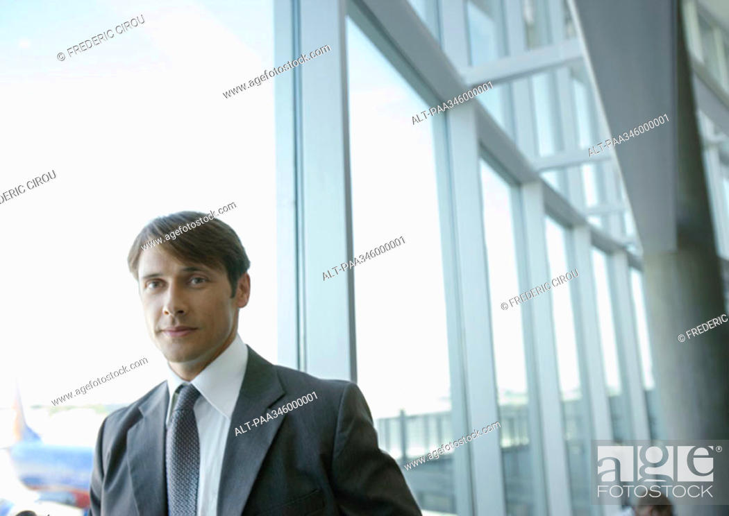 Stock Photo: Businessman by window in airport.