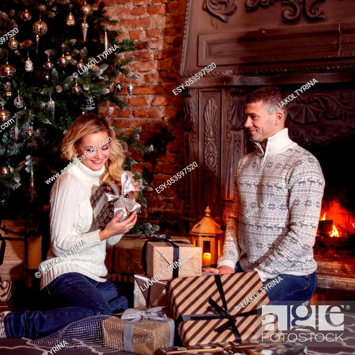 Photo de stock: Man and woman in knitted sweater sitting on the floor by the fireplace.