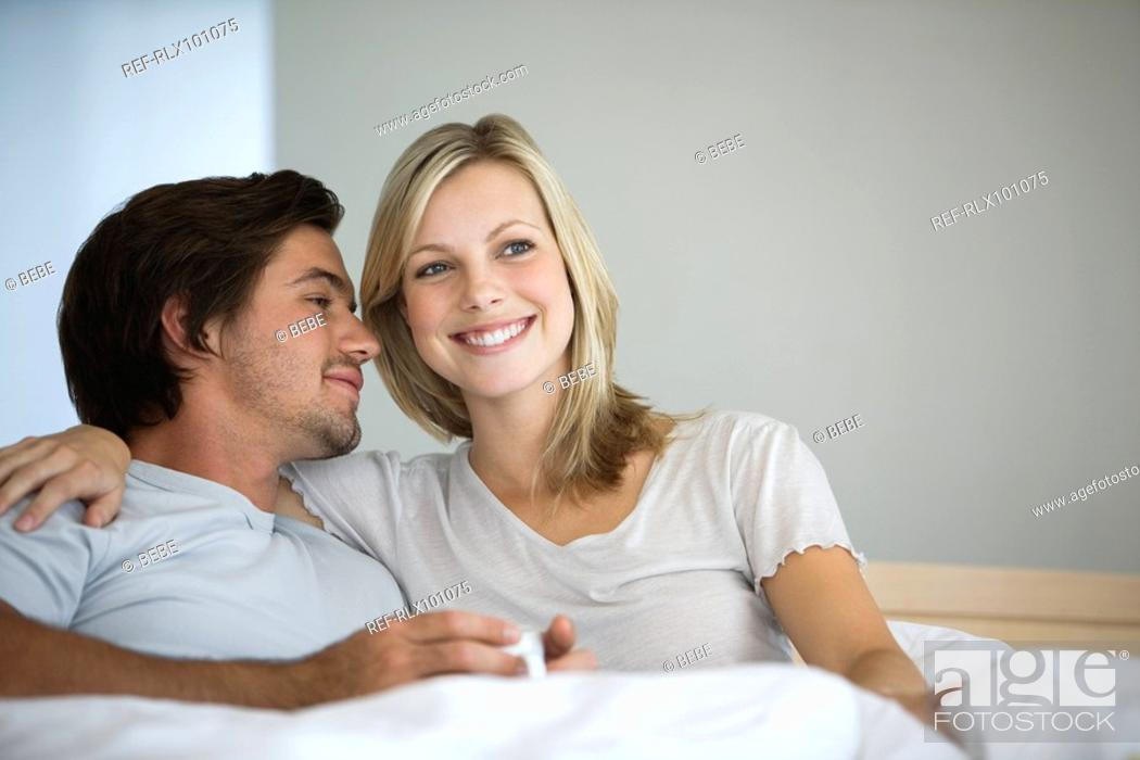 Stock Photo: Young couple sitting on bed, smiling, hugging, drinking coffee.