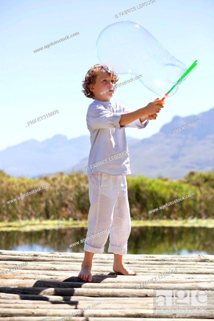 Stock Photo: Boy playing with a bubble wand at a pier.