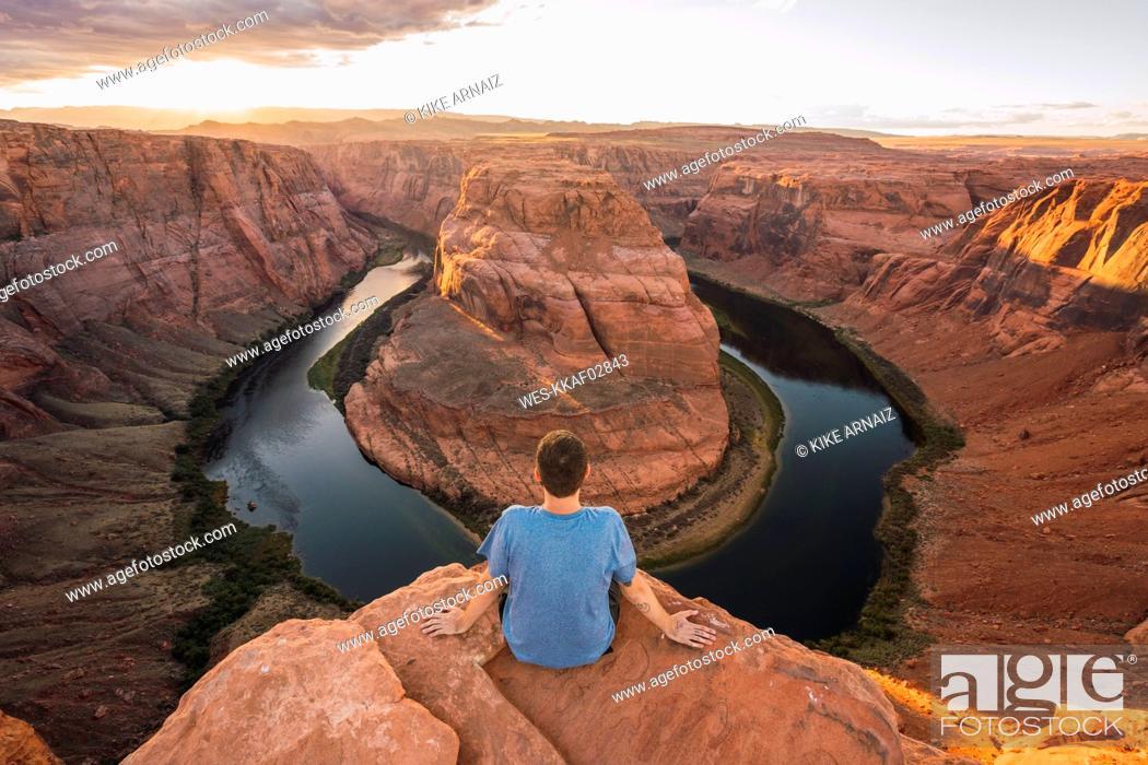Stock Photo: USA, Arizona, Colorado River, Horseshoe Bend, young man sitting on viewpoint.