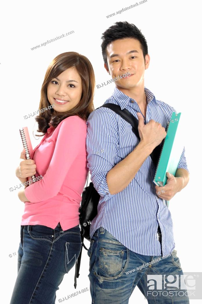 Stock Photo: University students standing back to back and smiling.