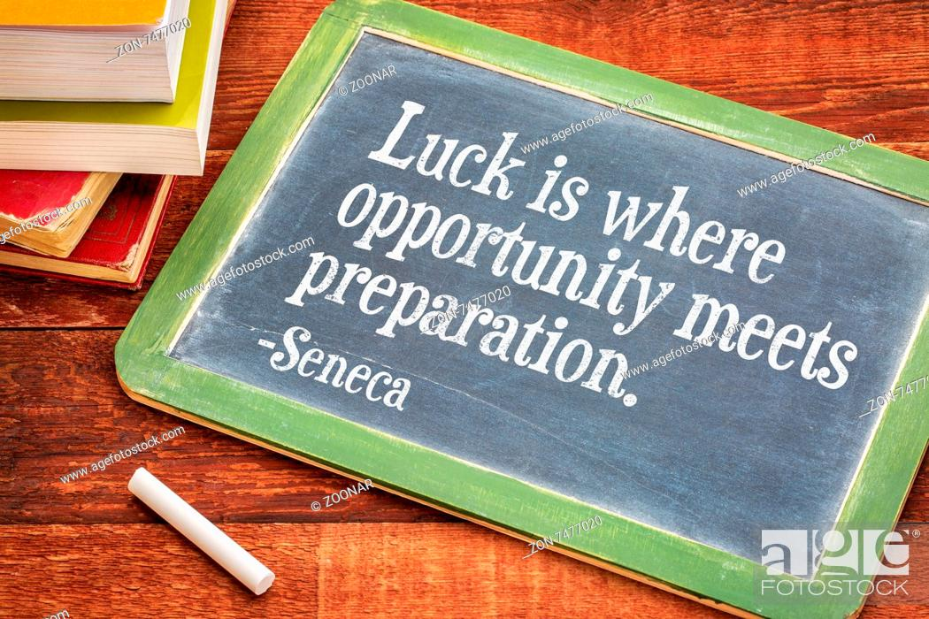 Imagen: Luck is where opportunity meets preparation - Seneca quote on a slate blackboard with a white chalk and a stack of books against rustic wooden table.