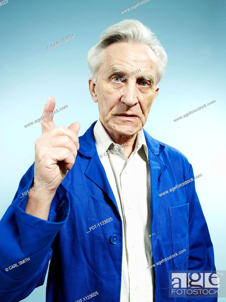 Stock Photo: A senior man wearing coveralls and pointing while talking.