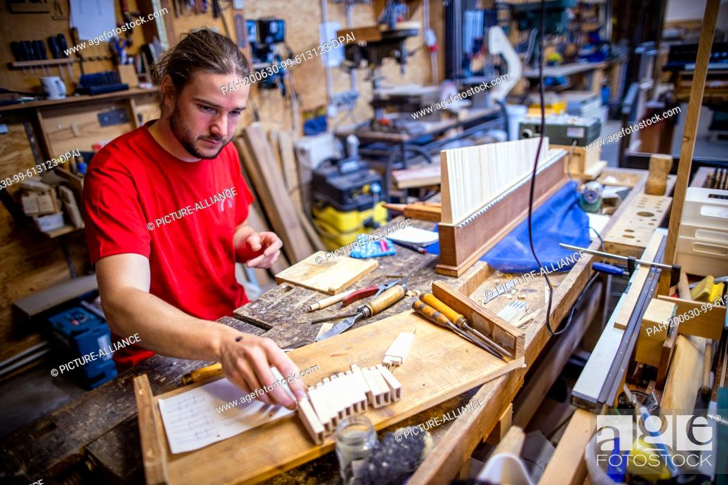 Stock Photo: 22 June 2020, Mecklenburg-Western Pomerania, Rostock: Jan Schumacher is working on reed pipes for the new construction of a chest organ in the workshop.