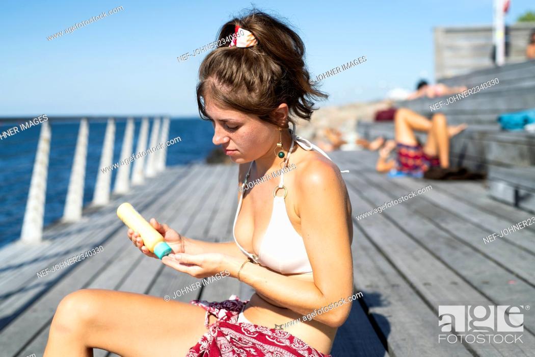 Stock Photo: Young woman applying sun protector.