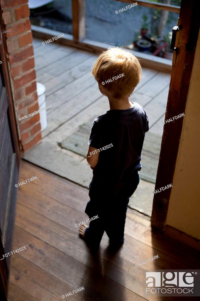 Stock Photo: A young boy standing in an open doorway.