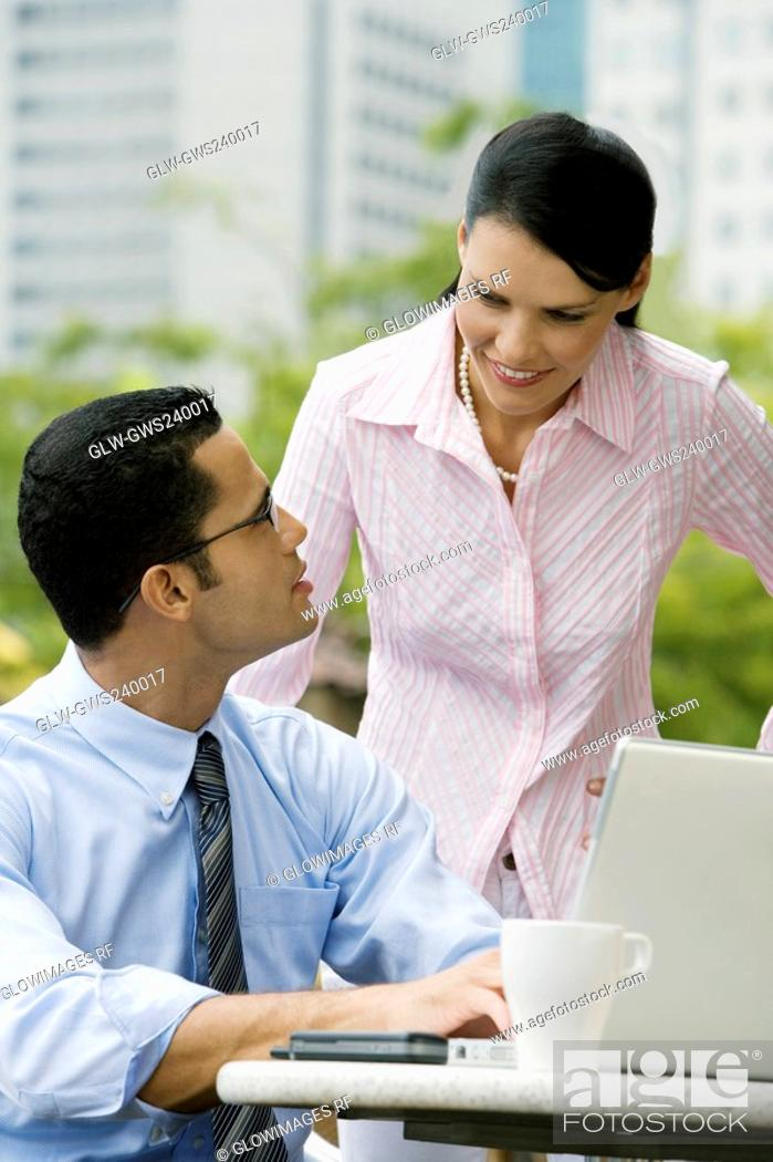 Stock Photo: Businessman using a laptop with a businesswoman standing beside him.