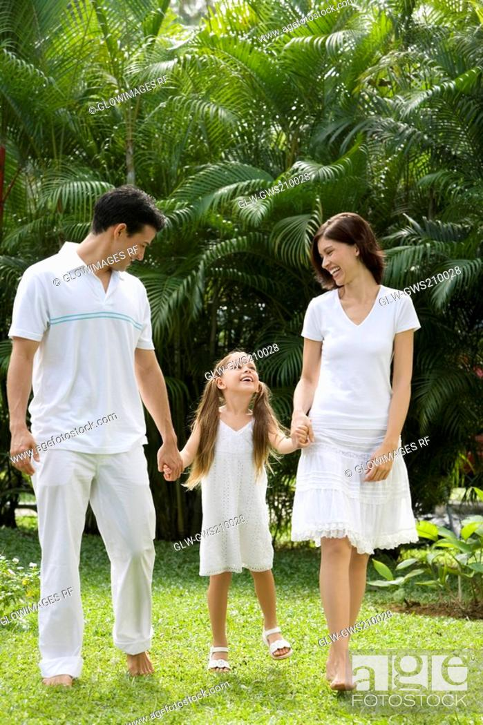 Stock Photo: Young couple walking with their daughter in a garden.
