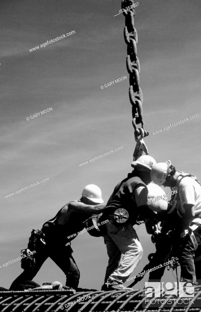 Stock Photo: Ironworkers attaching load to crane. I-880 Cypress Project. Oakland, California. USA.