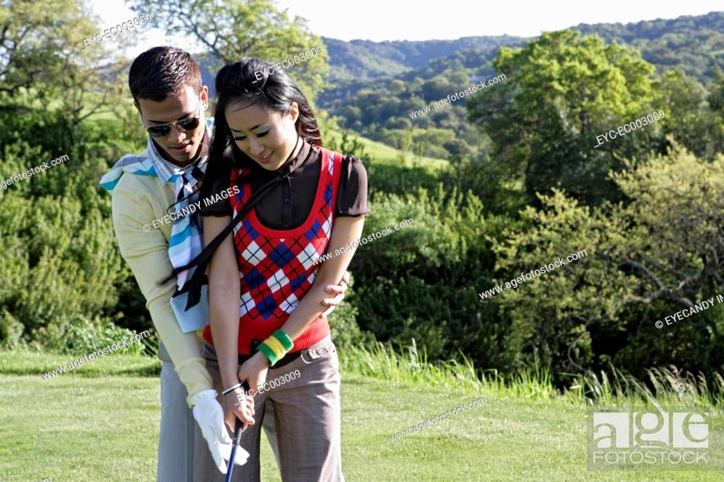 Stock Photo: View of a man teaching golf game to a woman.