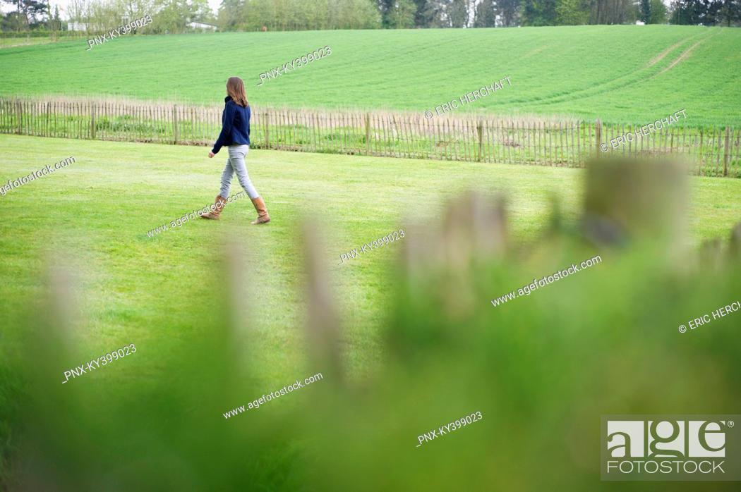 Stock Photo: Girl walking in a field.