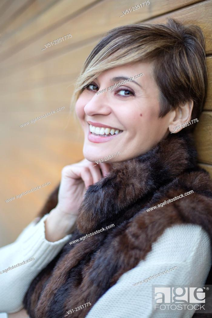 Stock Photo: Portrait of a stylish woman outdoors smiling at camera.